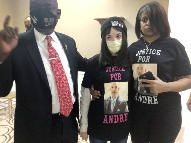 Attorney Benjamin Crump, left, discusses the police shooting of Andre Hill at a news conference attended by Hill's daughter, Karissa, center, and sister Shawna Barnett, on Thursday.