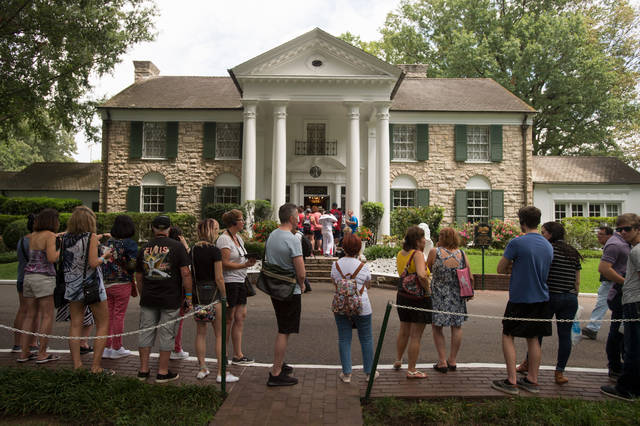 FILE - In an Aug. 15, 2017 file photo, fans wait in line outside Graceland, Elvis Presley's Memphis home, in Memphis, Tenn. Elvis Presley's Graceland says it will reopen Thursday, May 21, 2020 after it shut down tours and exhibits due to the new coronavirus outbreak. The tourist attraction in Memphis, Tennessee, said Sunday that it has adjusted its tours, and restaurant and retail operations, since it closed in March. (AP Photo/Brandon Dill, File)