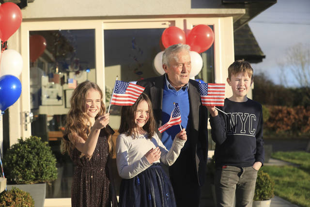 Joe Biden's cousins Brendan Blewitt with his grandchildren Emily, Lauren, and Darragh wave their U.S. flags to the media from their home in Knockmore, near the town of Ballina in Ireland, Wednesday, Jan. 20, 2021. Biden has officially become the 46th president of the United States. His great-great grandfather Patrick Blewitt was born in, County Mayo, in 1832. He left for the US in 1850, aged 18. (AP Photo/Peter Morrison)