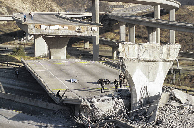 FILE - In this Jan. 17, 1994, file photo, the covered body of Los Angeles Police Officer Clarence Wayne Dean lies near his motorcycle which plunged off the State Highway 14 overpass that collapsed onto Interstate 5, after a magnitude-6.7 Northridge earthquake in Los Angeles.