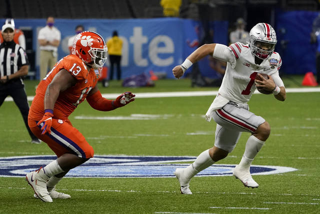 Ohio State quarterback Justin Fields runs past Clemson defensive tackle Tyler Davis during the first half of the Sugar Bowl NCAA college football game Friday in New Orleans. (AP Photo/John Bazemore)