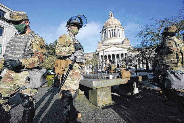 Members of the Washington National Guard stand at a sundial near the Legislative Building, Sunday, Jan. 10, 2021, at the Capitol in Olympia, Wash. Governors in some states have called out the National Guard, declared states of emergency and closed their capitols over concerns about potentially violent protests.