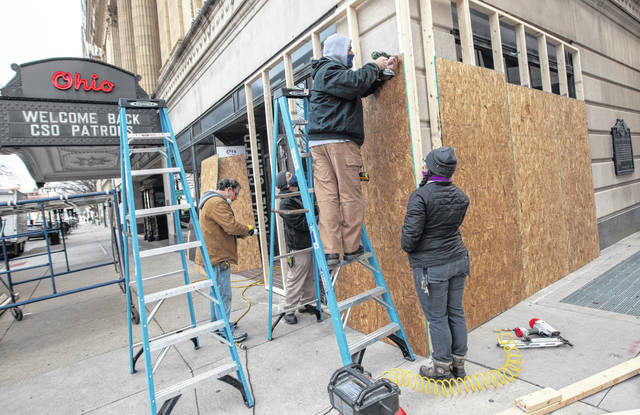 Stagehands from the Ohio Theatre board up the building's windows in preparation for planned weekend protests in Columbus on Thursday, Jan. 14, 2021.
