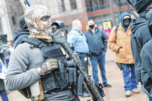 An armed protestor stands outside the Ohio Statehouse Sunday, Jan. 17, 2021, in Columbus, Ohio. Security was stepped up at statehouses across the U.S. after FBI warnings of potential armed protests at all 50 state capitols and in Washington, D.C.