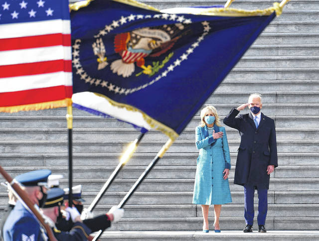 President Joe Biden salutes as his wife, Jill, puts her hand over her heart as they review the troops from the steps of the U.S. Capitol during the inauguration Wednesday.