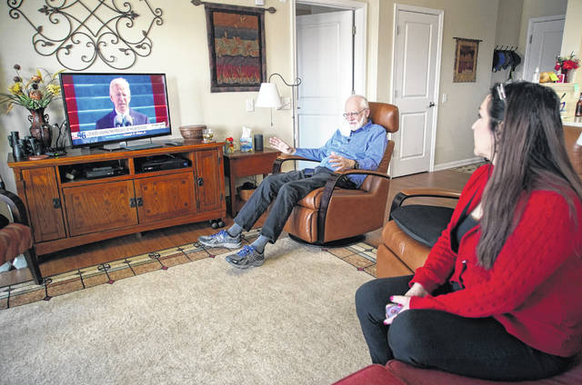 Democrat Jim Carpenter, left, and Republican Natalie Abbas watch the inauguration of President Joe Biden in Carpenter's apartment in Frederick, Md., on Wednesday. The two are local ambassadors for a program designed to bridge the nation's extraordinary political divide.