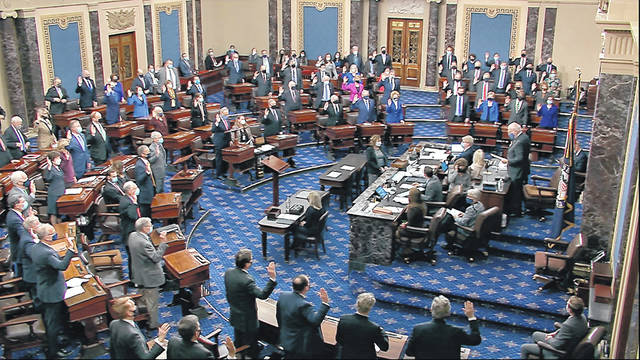 In this image from video, Sen. Patrick Leahy, D-Vt., the president pro tempore of the Senate, who is presiding over the impeachment trial of former President Donald Trump, swears in members of the Senate for the impeachment trial at the U.S. Capitol in Washington, Tuesday, Jan. 26, 2021.