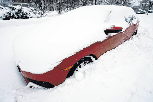 A car is covered by snow in Wheeling, Ill., Sunday, Jan. 31, 2021. Winter storm may leave more than 1 foot of snow in Chicago area before it's over, flight cancellations stack up, roads remain hazardous.