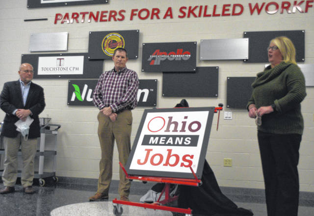 Keith Horner, superintendent of Apollo Career Center (left) joins Joe Patton and Amy Freymuth in unveiling a plaque honoring Ohio Means Jobs' partnership with the vocational school.