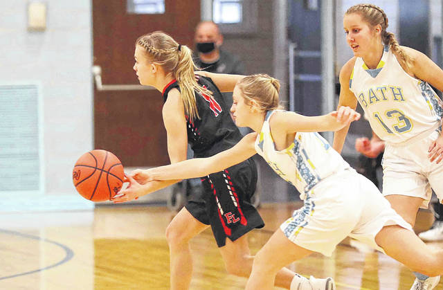 Bath's Lexi Renner knocks the ball away from Fort Loramie's Caitlyn Gasson during Saturday's game at Bath. Also defending for Bath is Esther Bolon (13). See more game photos at LimaScores.com.
