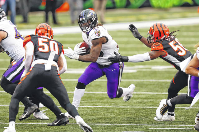 Baltimore Ravens running back Gus Edwards (35) runs between Cincinnati Bengals outside linebacker Jordan Evans (50) and middle linebacker Josh Bynes (56) during the Ravens' 38-3 win over the Bengals on Sunday in Cincinnati.