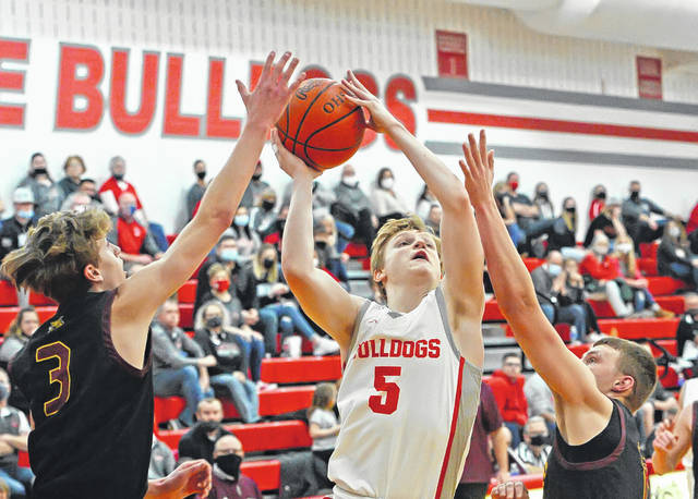 Columbus Grove's Gabe Clement puts up a shot against Kalida's Brandon Miller, left, and Tyson Siefker during Saturday night's game at Columbus Grove. See more game photos at LimaScores.com.