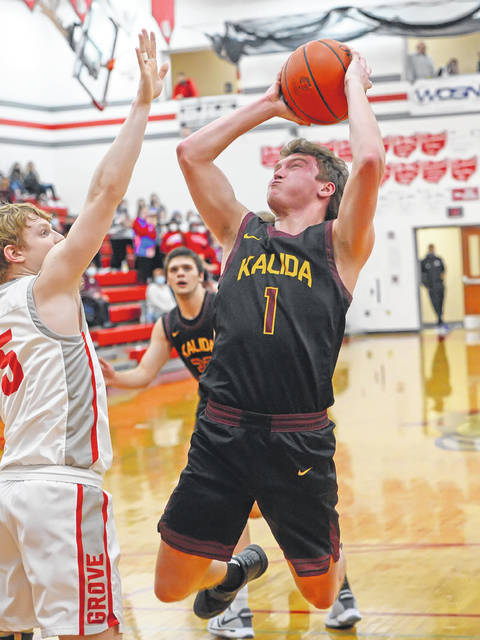 Kalida's Ayden Warnecke puts up a shot against Columbus Grove's Gabe Clement during Saturday night's game at Columbus Grove.