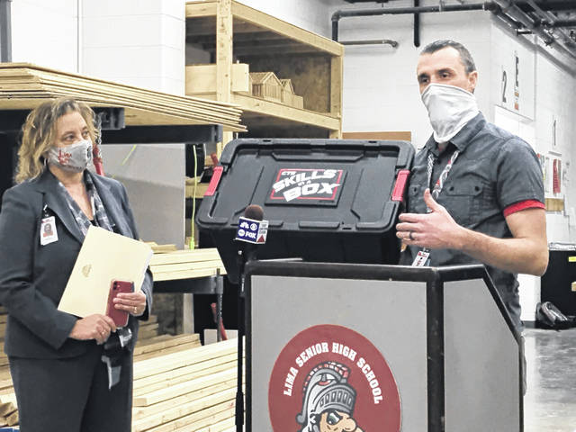 Lima schools career tech director Courtnee Morris, right, unveils a prototype of a skills box while Lima Superintendent Jill Ackerman looks on. The box contains a series of elementary-level lessons designed to help young students master basic trade skills before entering high school. It's one part of the school district's effort to expand career programming.