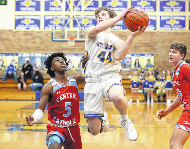Landon Grothaus of Delphos St. John's puts up a shot against Lima Central Catholic's DeMarr Foster during Tuesday night's game at DSJ. See more game photos at LimaScores.com.
