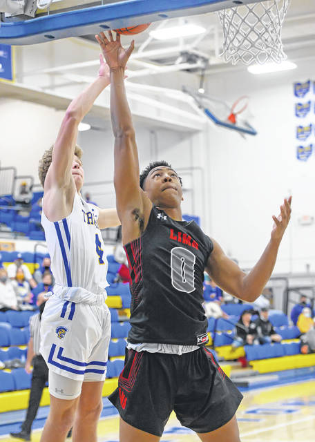 Lima Senior's Anthony Mosely puts up a shot against Findlay's Max Roth during Friday night's game at Findlay.