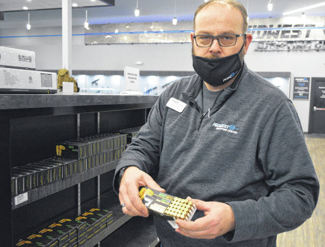 John Drake, assistant manager with Midwest Shooting Center in Cridersville, shows some of the ammo they have in stock.