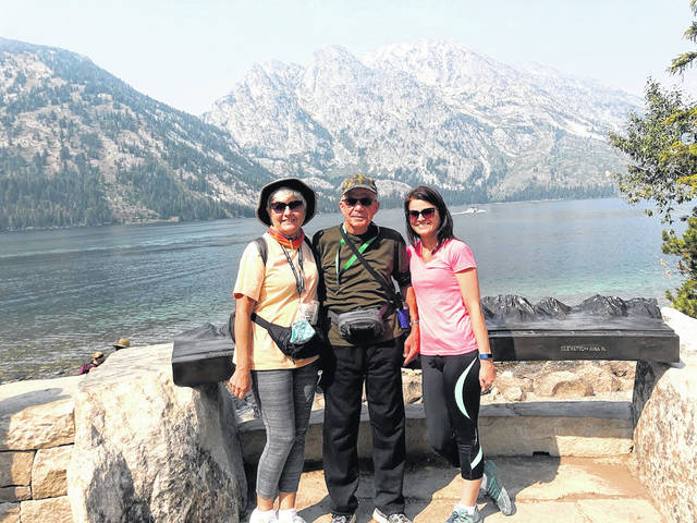 Georgia, Linus and Sherry Rindler at Jenny Lake overlook, Grand Teton National Park, Wyoming, with Grand Tetons in distance.