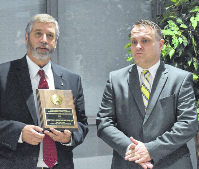 Steve Stechschulte, a 30-year member of the Lima Police Department, was honored Wednesday with the Ohio Prosecuting Attorneys Association award as Outstanding Peace Officer for 2020. Presenting the award was Allen County Prosecuting Attorney Juergen Waldick, left.