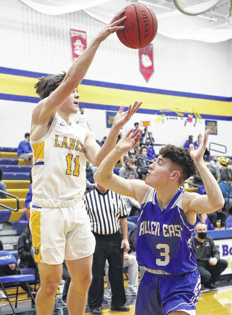 Lincolnview's Collin Overholt makes a pass against Allen East's Kaden Armstrong (3) during Friday night's game at Lincolnview.