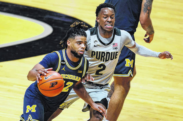 Michigan guard Mike Smith (12) drives on Purdue guard Eric Hunter Jr. (2) during the Wolverines' men's basketball 70-53 win over the Boilermakers on Friday night. The appearance of a new variant of COVID-19 in some positive tests has led Michigan to pause all athletic activities for two weeks.