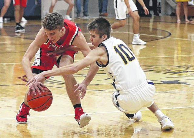 Bluffton's Trey Boblitt, left, and Ottawa-Glandorf's Eli Schmenk go for a lose ball during Saturday night's game at Ottawa-Glandorf. See more game photos at LimaScores.com.
