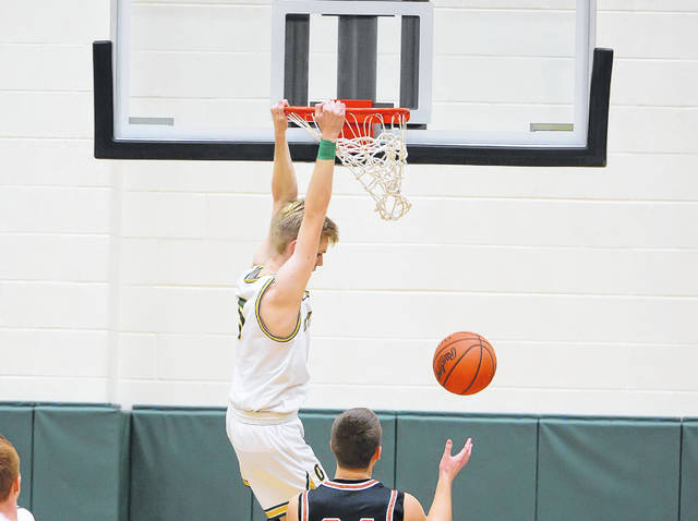 Ottoville's Ryan Suever scores on a dunk during Friday night's game against Fort Jennings at Ottoville. Head to LimaScores.com for more game photos.