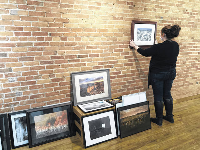 Maia Fisher works to hang the show, the Juried Photography Exhibition.