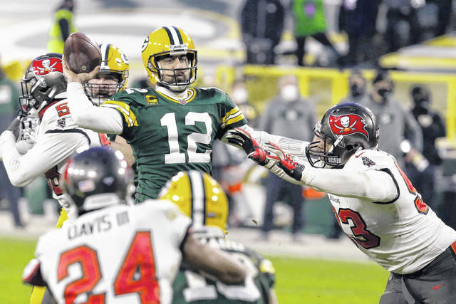 Green Bay Packers quarterback Aaron Rodgers (12) evades a pass rusher and looks for a receiver against the Tampa Bay Buccaneers during the NFL championship game on Sunday in Lambeau Field in Green Bay, Wisconsin.