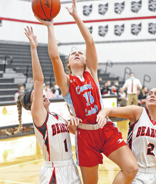 Lima Central Catholic's Olivia Stolly shoots past Spencerville's Gillian Goecke, left, and Lilyan Goecke during Monday's game at Spencerville High School. Stolly finished with 21 points.