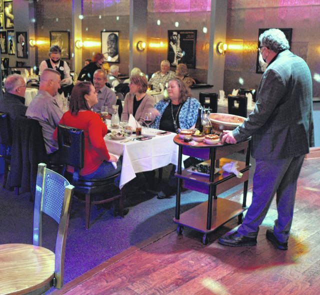 John Heaphy, owner of Old City Prime, serves guests at his restaurant Saturday night.