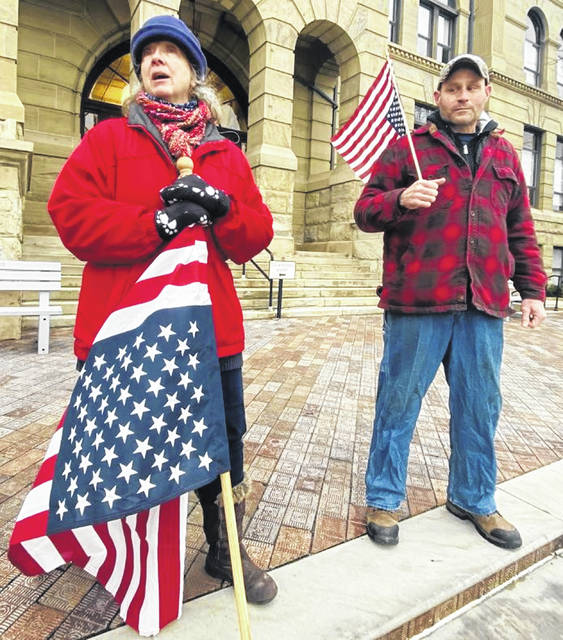 Laurie Smith, of Waynesfield, and Tony Homan, of St. Marys, protested at the Auglaize County Courthouse in Wapakoneta on Wednesday with upside-down flags as rioters stormed the U.S. Capitol.