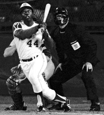 The Atlanta Braves' Hank Aaron watches his record setting 715th career homer in a game against the Los Angeles Dodgers in Atlanta on April 8, 1974, off pitcher Al Downing. Catcher Joe Ferguson and umpire David Davidson also watch the flight of the ball.