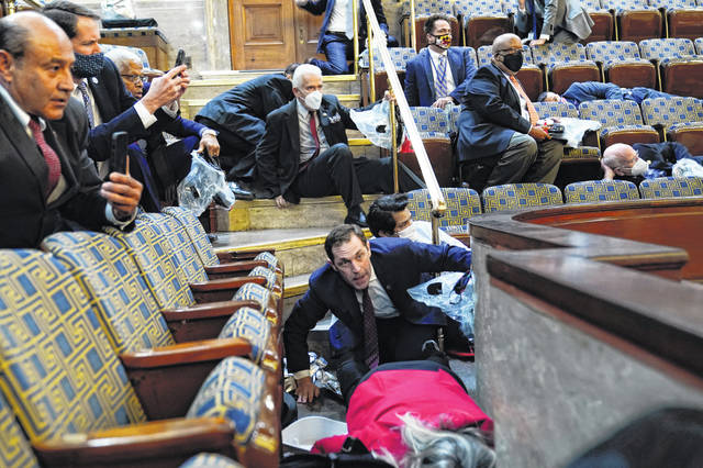 People shelter in the House gallery as protesters try to break into the House Chamber at the U.S. Capitol on Wednesday.