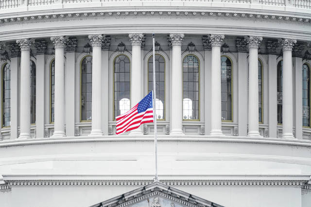 An American flag flies at half-staff in remembrance of U.S. Capitol Police Officer Brian Sicknick above the Capitol Building in Washington.