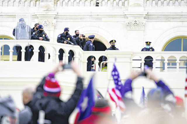 Police keep a watch on demonstrators who tried to break through a police barrier, Wednesday, Jan. 6, 2021, at the Capitol in Washington. As Congress prepares to affirm President-elect Joe Biden's victory, thousands of people have gathered to show their support for President Donald Trump and his claims of election fraud. (AP Photo/Julio Cortez)
