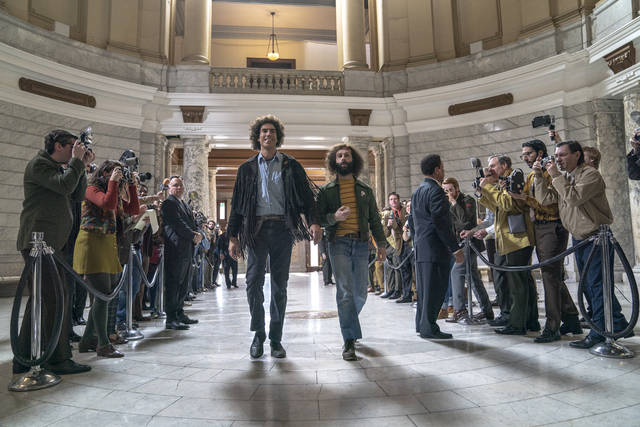 """This image released by Netflix shows Sacha Baron Cohen, center left, and Jeremy Strong in a scene from """"The Trial of the Chicago 7."""" The Screen Actors Guild has nominated the cast for a SAG Award for outstanding performance by a cast in a motion picture. (Niko Tavernise/Netflix via AP)"""