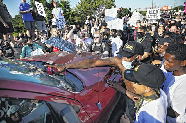 Protesters surround a truck May 31, 2020, on Interstate 244 in Tulsa, Okla. The group was protesting the killing of George Floyd by Minneapolis police on May 25 and commemorating the 1921 Tulsa Race Massacre.