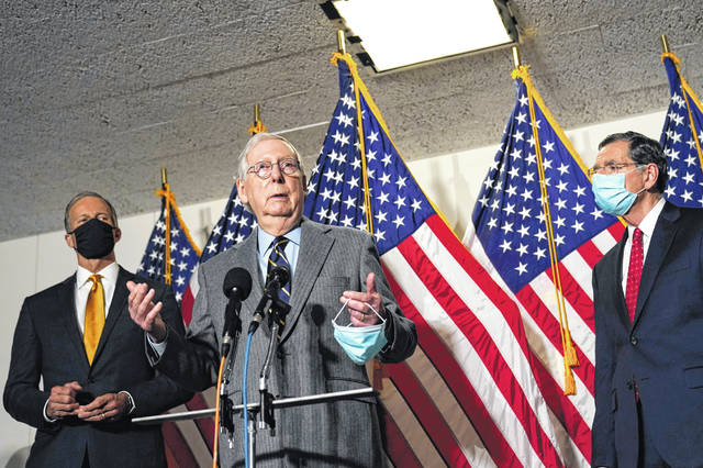 Senate Minority Leader Mitch McConnell of Ky., center, flanked by Sen. John Thune, R-S.D., left, and Sen. John Barrasso, R-Wyo., right, speaks during a news conference on Capitol Hill in Washington, Tuesday, Jan. 26, 2021.