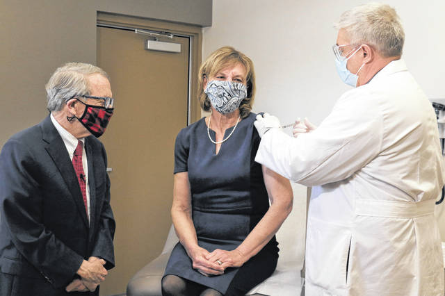 Ohio Governor Mike DeWine, left, looks on as first lady Fran DeWine receives her COVID-19 vaccination from Dr. Kevin Sharrett, Tuesday, 2, 2021, in Jamestown, Ohio. The DeWines became eligible to receive their first shot this week as vaccinations are now open to Ohioans age 70 and above.
