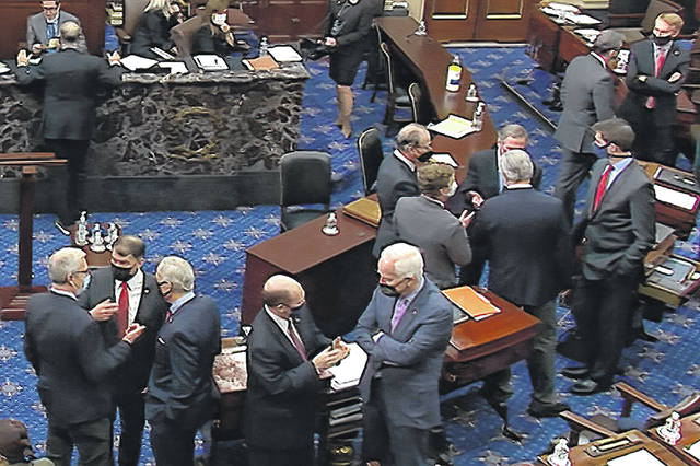 In this image from video, Republican senators and staff talk on the floor after a vote on the motion to allow witnesses in the second impeachment trial of former President Donald Trump in the Senate at the U.S. Capitol in Washington, Saturday, Feb. 13, 2021.
