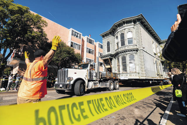 A worker signals to a truck driver pulling a Victorian home through San Francisco on Sunday, Feb. 21, 2021. The house, built in 1882, was moved to a new location about six blocks away to make room for a condominium development. According to the consultant overseeing the project, the move cost approximately $400,000 and involved removing street lights, parking meters and utility lines.