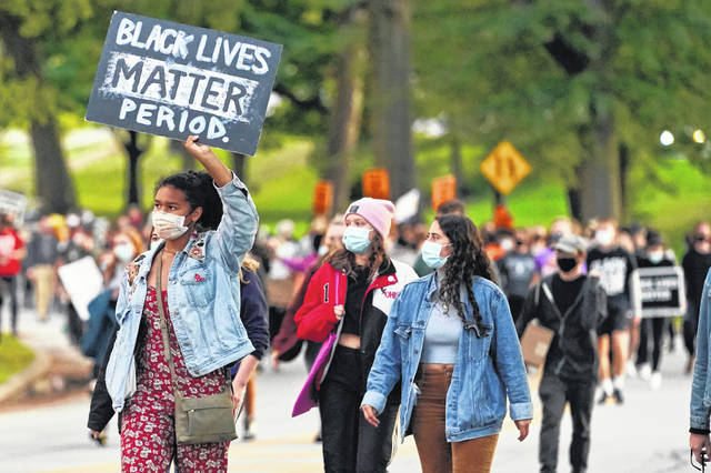A woman holds up a sign during q protest, Tuesday, Sept. 29, 2020, in Cleveland. Racism would be declared a public health crisis in Ohio and the day celebrating the official end of slavery would become a paid state holiday under racial justice measures reintroduced Tuesday, Feb. 23, 2021, after unsuccessful efforts to pass them during the last legislative session.