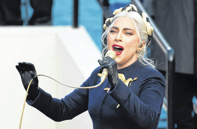 FILE - Lady Gaga sings the national anthem during President-elect Joe Biden's inauguration at the U.S. Capitol in Washington on Jan. 20, 2021. Officials say Lady Gaga's dog walker was shot and her two French bulldogs stolen in Hollywood during an armed robbery. Los Angeles police are seeking two suspects, thought it's not known if both were armed, in connection with the Wednesday night shooting.