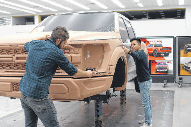 A 2021 F-150 Raptor clay model is being worked on by exterior designer Tom Liu, right, and clay modeler Josh Brooker at the Ford Product Development Center in 2019 in Dearborn.