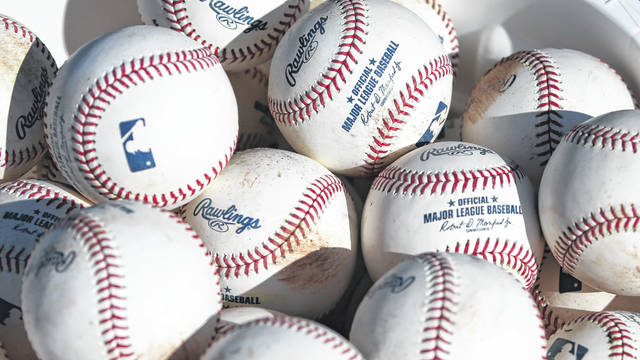 Baseballs sit in a bucket after they were used for fielding practice during spring training baseball workouts for pitchers and catchers at Cleveland Indians camp in Avondale, Ariz., last year. Major League Baseball revamped its spring training exhibition schedule this year because of the pandemic, cutting travel for Florida-based teams in an effort to avoid the novel coronavirus.