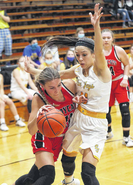 Delphos Jefferson Girls Basketball #21 Josie McGue drives the baseline against Delphos Saint John's Girls Basketball #11 Paige Gaynier late in the first quarter at Delphos Saint John's High School on November 20, 2020 more photos are available at limanews.com Photo By Don Speck