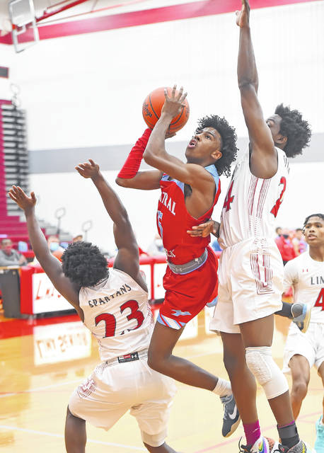 Lima Central Catholic's Demarr Foster puts up a shot against Lima Senior's Jourdyn Rawlins, left, and Quan Moore during Saturday night's game at Lima Senior.