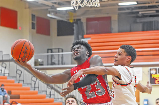 Lima Senior's Jourdyn Rawlins puts up a shot against Mansfield Senior's D'Angelo Chapman during Tuesday night's game in Mansfield.