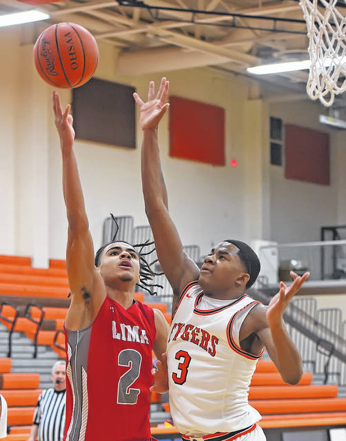 Lima Senior's Jereon Mayo puts up a shot against Mansfield Senior's Maurice Ware during Tuesday night's game in Mansfield.